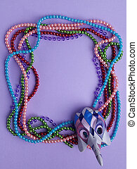 Mardi Gras beads and mask making a frame with copy space on purple background.Flat lay. Top view