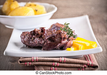 Rabbit in winy sauce with potato on a white plate. - Rabbit...