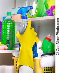 Woman putting spray bottle in pantry - Woman with safety...