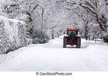 Tractor driving down a snow covered road - A red tractor...