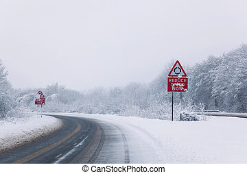 Road with Reduce speed now sign during snow fall of winter...