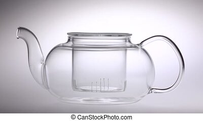 Two tablespoons of tea poured in transparent teapot. White...