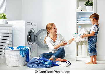family mother and child girl in laundry room near washing...