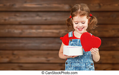 happy laughing child girl with gift Valentine's Day, wooden...