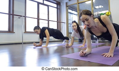 Woman lying on hands doing exercises for hands in gym....