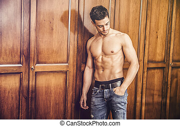 Sexy handsome young man standing shirtless against wardrobe...