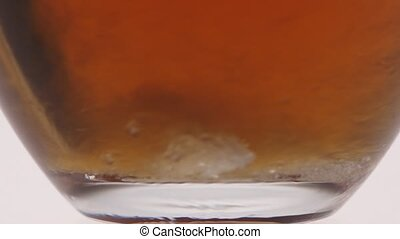 Closeup. Undissolved sugar at the bottom glass cup with tea...