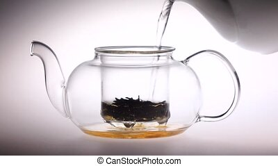 Boiling water is poured into glass teapot with tea leaves