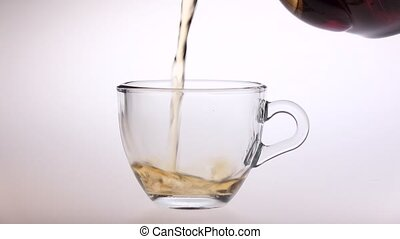 Tea is poured from a teapot into small glass cup