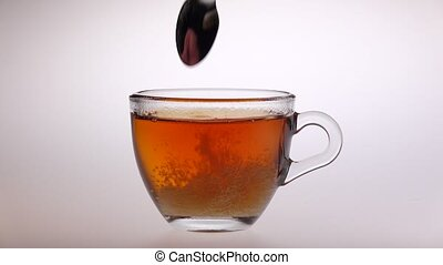 Sugar stir in glass cup with tea of a spoon, man hand...