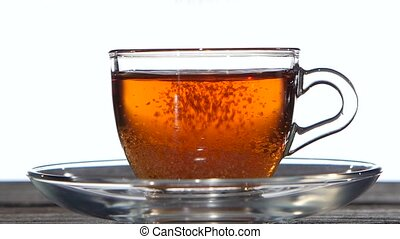 In cup of tea add sugar spoon. Closeup. Slow motion