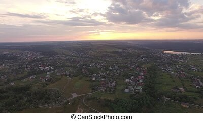 Aerial view of Suburban town next to a river and fields at sunset in summer
