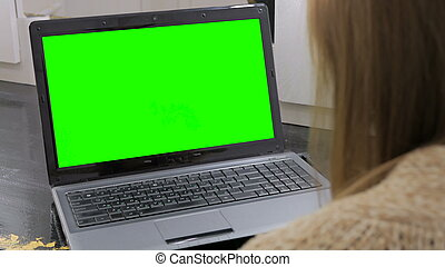 Woman looking at laptop with green screen. Business,...