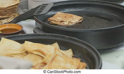 Cooking traditional russian pancakes on a skillet. Close up