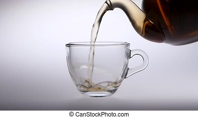 Tea is poured from a teapot into transparent glass cup - Tea...
