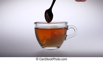 Sugar stir in a cup with tea of a spoon, man hand holding a...
