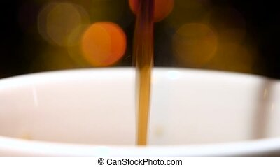 Pouring jet of black coffee in a cup. Closeup - Pouring jet...