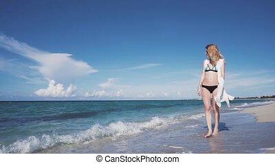 The beautiful blonde in a bikini walking on the beach