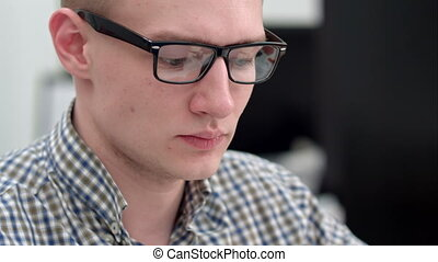 Young man in glasses working in the office. Close up shot....