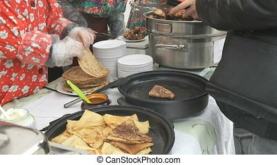 The saleswoman sells traditional russian pancakes - The...