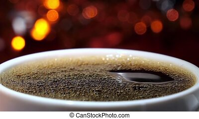 Cup filled hot freshly brewed black coffee. Closeup