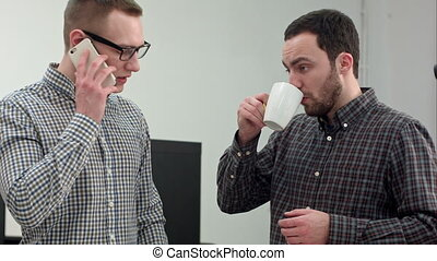 Two male architects discussing technical drawing drinking coffee