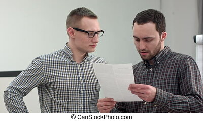 Two businessmen tearing up a document or contract....