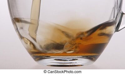 Closeup. Tea is poured into a transparent cup - Tea is...