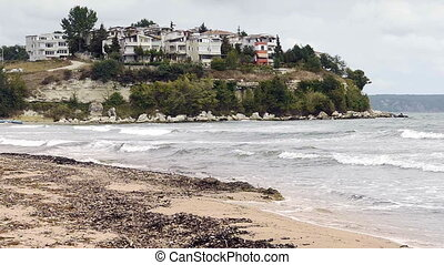 Coastal landscape with crushing waves and small town on hill...
