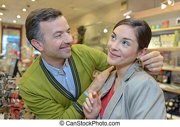 man attaching necklace to girls neck in retail store