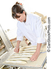 Bakery worker scoring bread