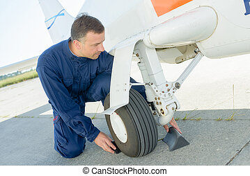Mechanic putting chocks around wheel of aircraft