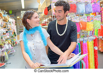 Couple browsing catalogue of fancy dress costumes