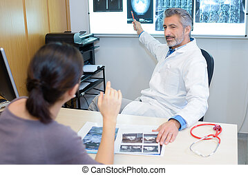 Radiologist pointing to images