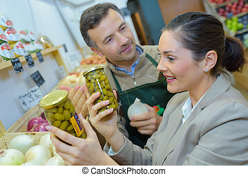 smiling woman choosing different fruits at farm food store...