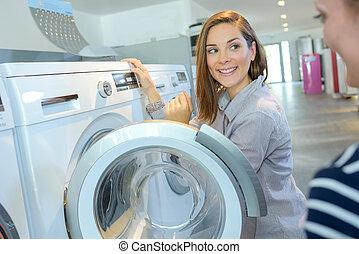 shopper choosing washing machine in household appliance...
