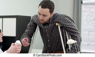 Young man with crutches looking at pills prescribed by...