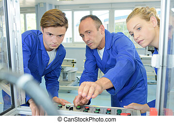 engineer showing apprentices how to operate machine