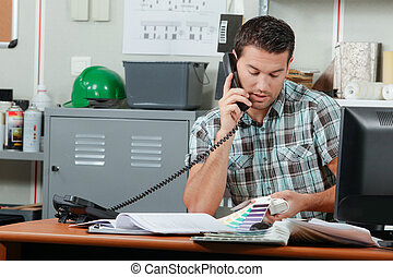 Man on telephone looking at color charts