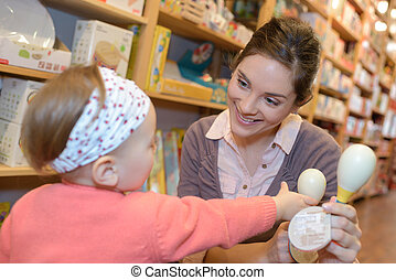 mother and daughter playing at toy store