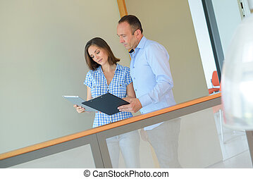 Couple in office corridor looking at clipboard