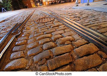 Railroad Tracks and Cobblestone Road - Railroad tracks on a...