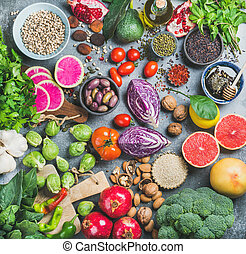 Healthy raw food variety over grey concrete background -...
