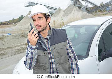 Man communicating via walkie talkie