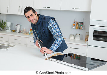 worker installing new induction hob in modern kitchen