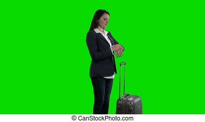 Woman with suitcase checking schedule on departure board...