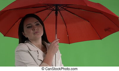 Chilled woman under red umbrella waiting against green...