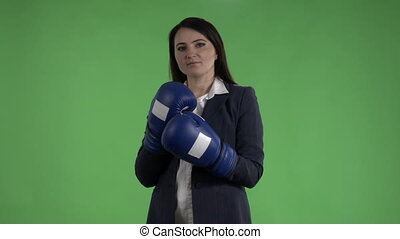 Business woman with boxing gloves punching against green screen slow motion