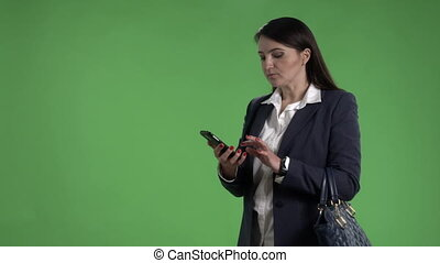 Business woman talking on the phone and waving to taxi against green screen