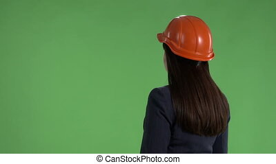 Business woman in safety helmet standing against green...